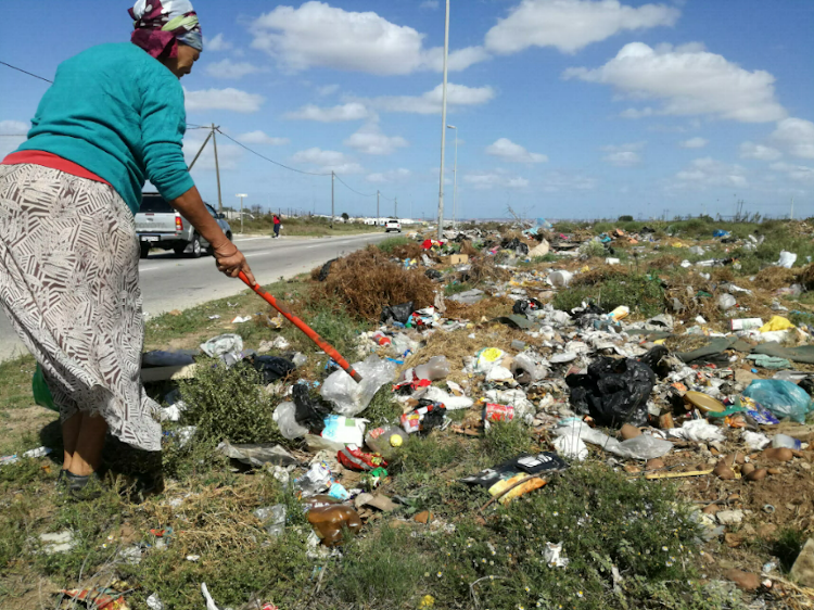 Wells Estate resident Susan Stoffels looks through waste in Malinga Street.