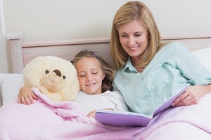 Mother reading to daughter at bedtime