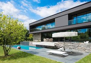 zwembad met modern zitje naast modern huis