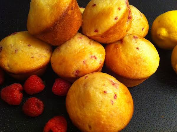 Seven To Eight Muffins With Raspberries On A Black Table Mat With A Lemon In The Background.