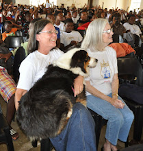 Photo: Dr. Elizabeth had just been up front speaking and her faithful dog could hardly stand it. As soon as she sat down the dog jumped up on her lap to keep her put. June McKinney beside her.