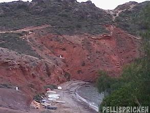 Photo: Röda bergen i en liten vik