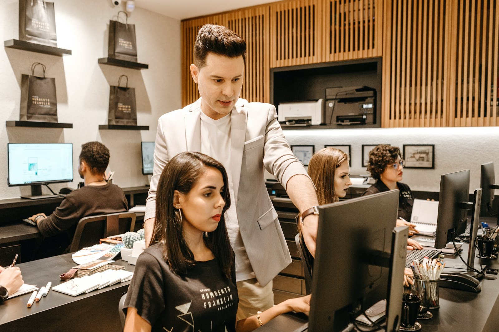 man teaching woman in front of monitor