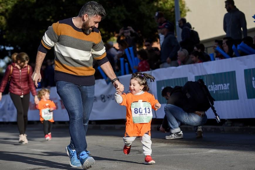 El papá corre con la pequeña.