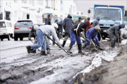 A municipal workers clean up the mud in Victoria road in Camps Bay after the storm cause havoc in Cape Town.Picture: ESA ALEXANDER 13/07/2009