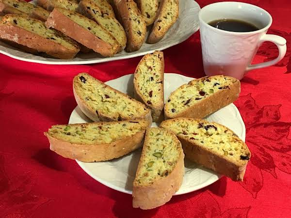 Six Biscotti On A Plate With More In The Background Along With A Cup Of Coffee.