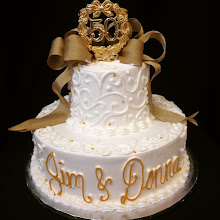 Photo: Fancy 2-tier stacked cake featuring white Town&Country w/gold dot border on both tiers w/writing on bottom tier. Gold French ribbon bow & 50th piece toppers.
