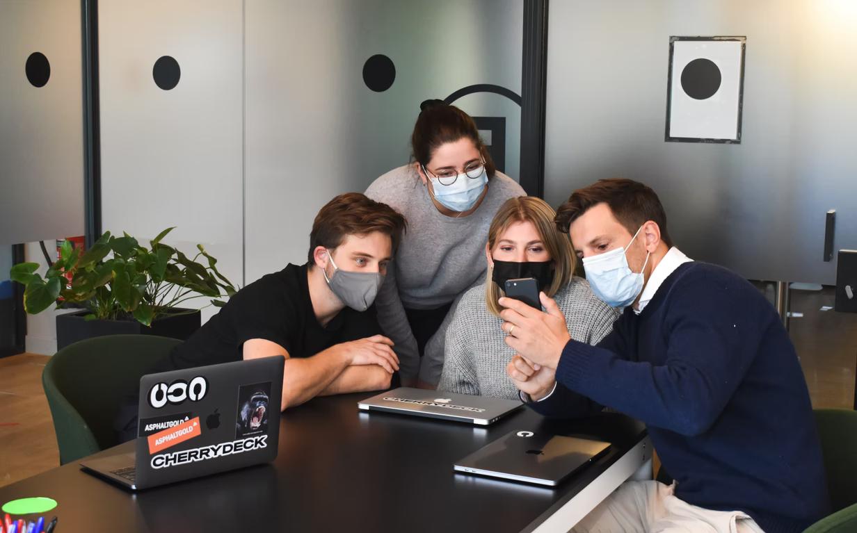 pracovný kolektív spolupracuje za stolom v rúškach na tvárach