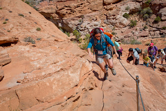 Photo: Debbie makes it up one of the steep sections, where footholds are carved out of the rock and there is a steel cable to hold onto.