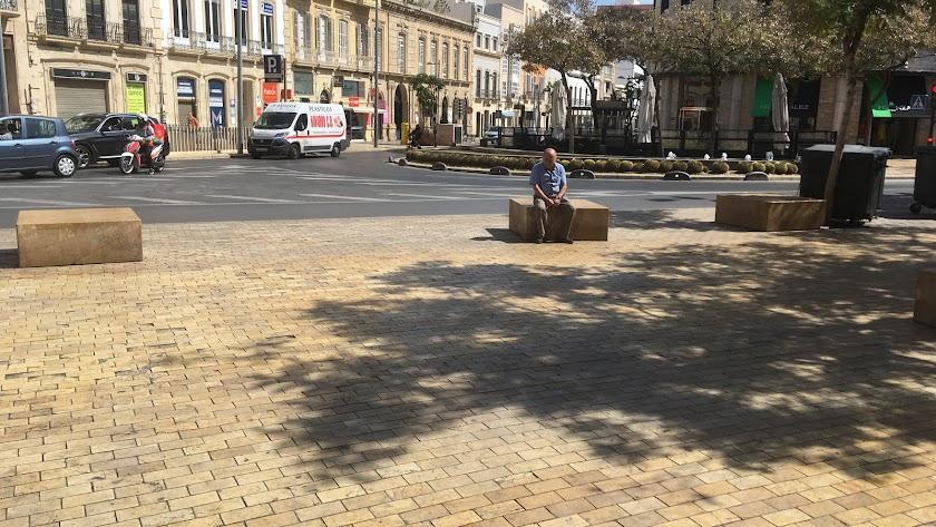 Un hombre sentado y solitario en un banco de piedra de la Puerta Purchena. Detrás, el centro de la ciudad que empieza a desperezarse.