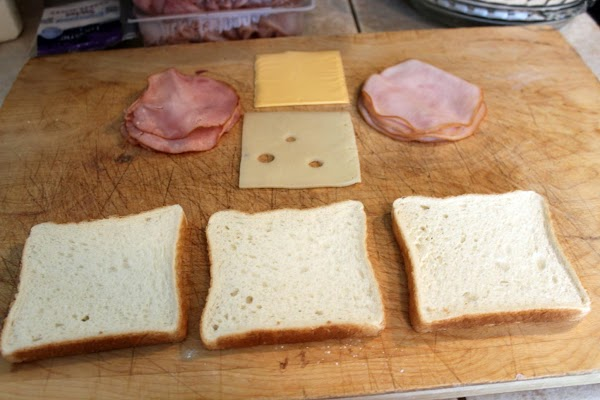 Assemble sandwiches in this order: bread, turkey, Swiss cheese, bread, ham, American cheese, bread.