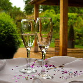 A glass of two of bubbly by Carol Henson - Wedding Details ( cloth, confetti, glasses, wedding, tray, depth of field, glass )