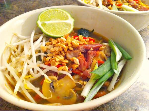 A Bowl Of Soup With Bean Sprouts, Mushrooms, Green Onions, Chopped Peanuts With Half A Lime For Garnish.