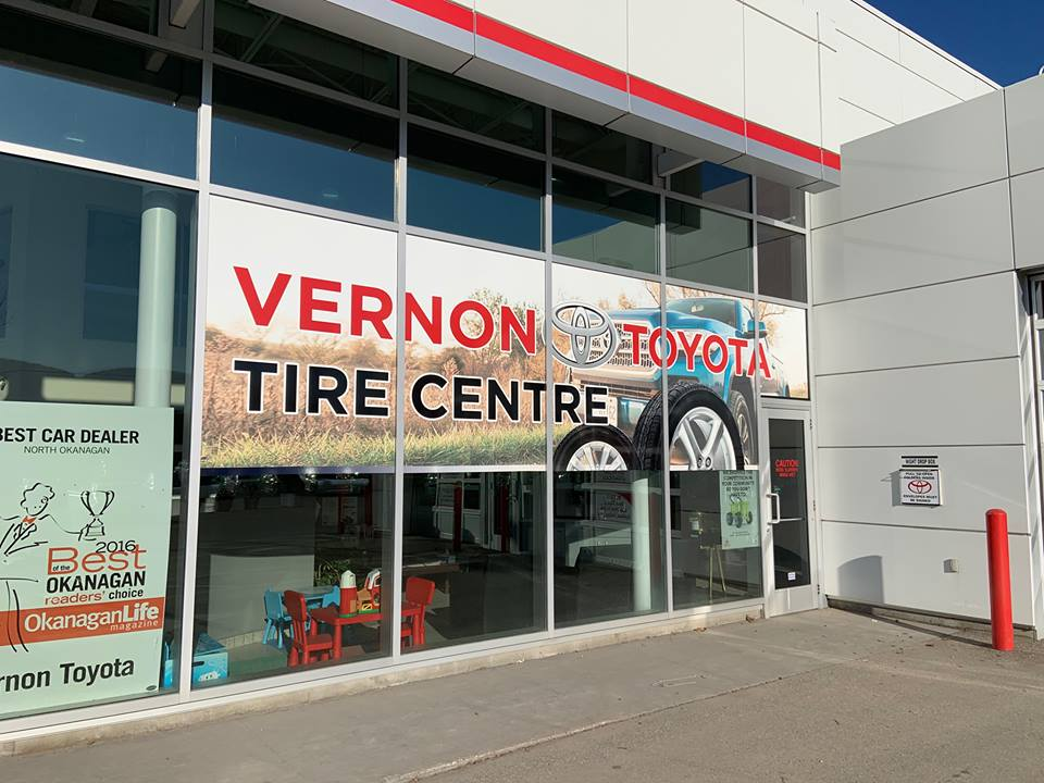"A Photo of Vernon Toyota's outside window with the sign ""Vernon Tire Centre"""