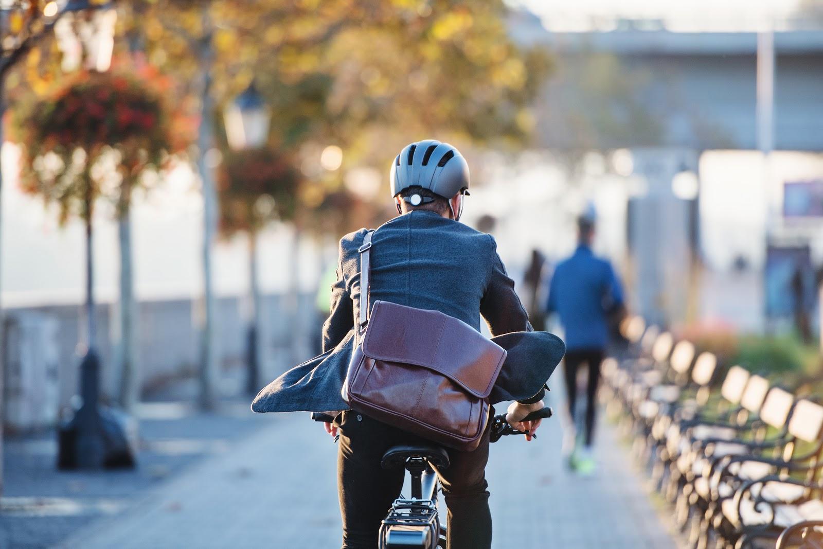 Homem andando de bicicleta com capacete e bolsa
