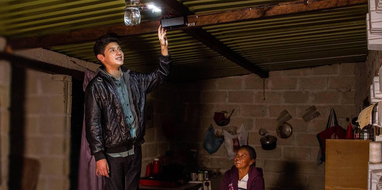 Un jóven estudiante se muestra orgulloso mostrando su invención.