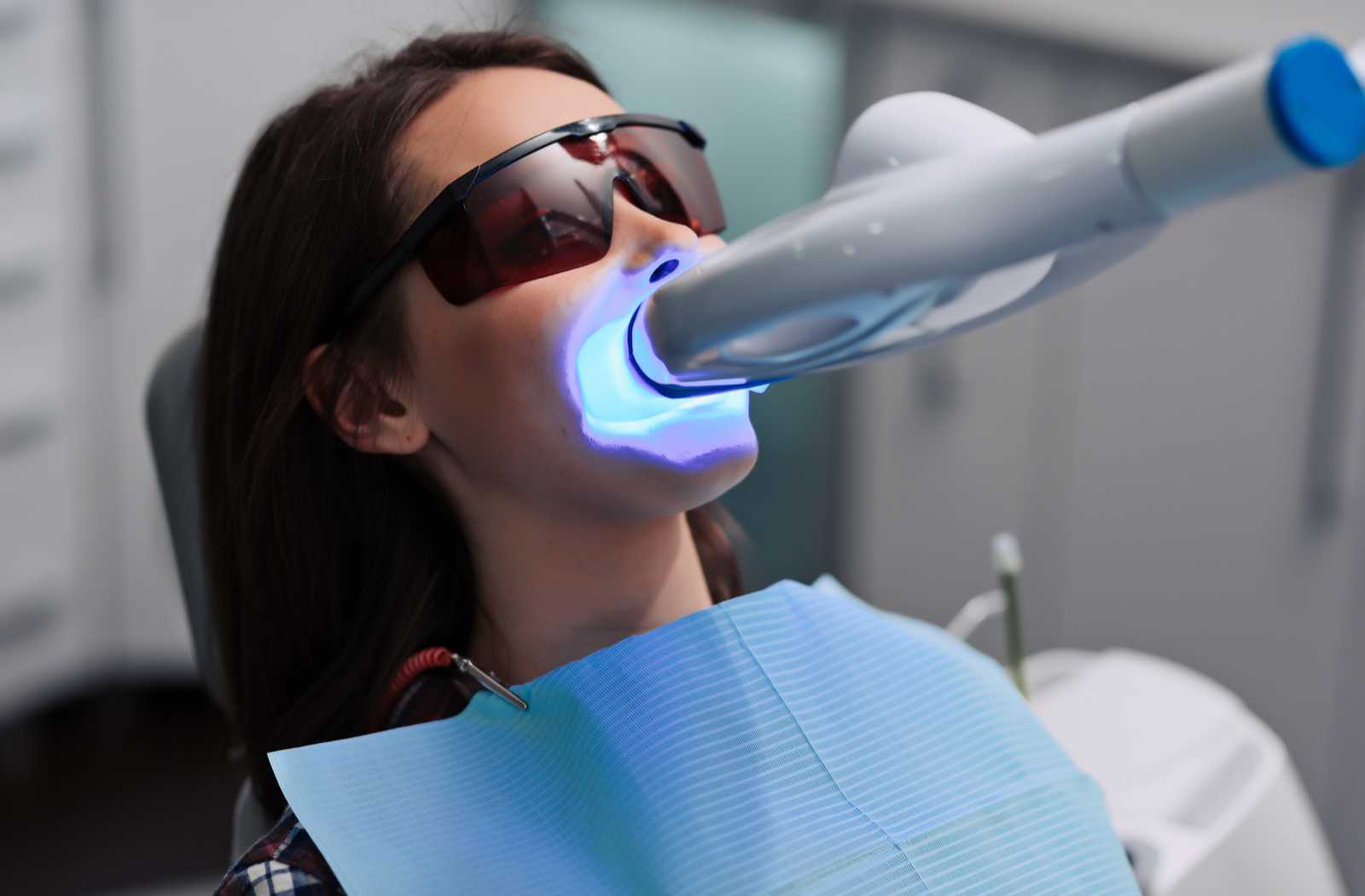 woman in dental chair with sunglasses and blue bib comfortably undergoing UV assisted bleaching