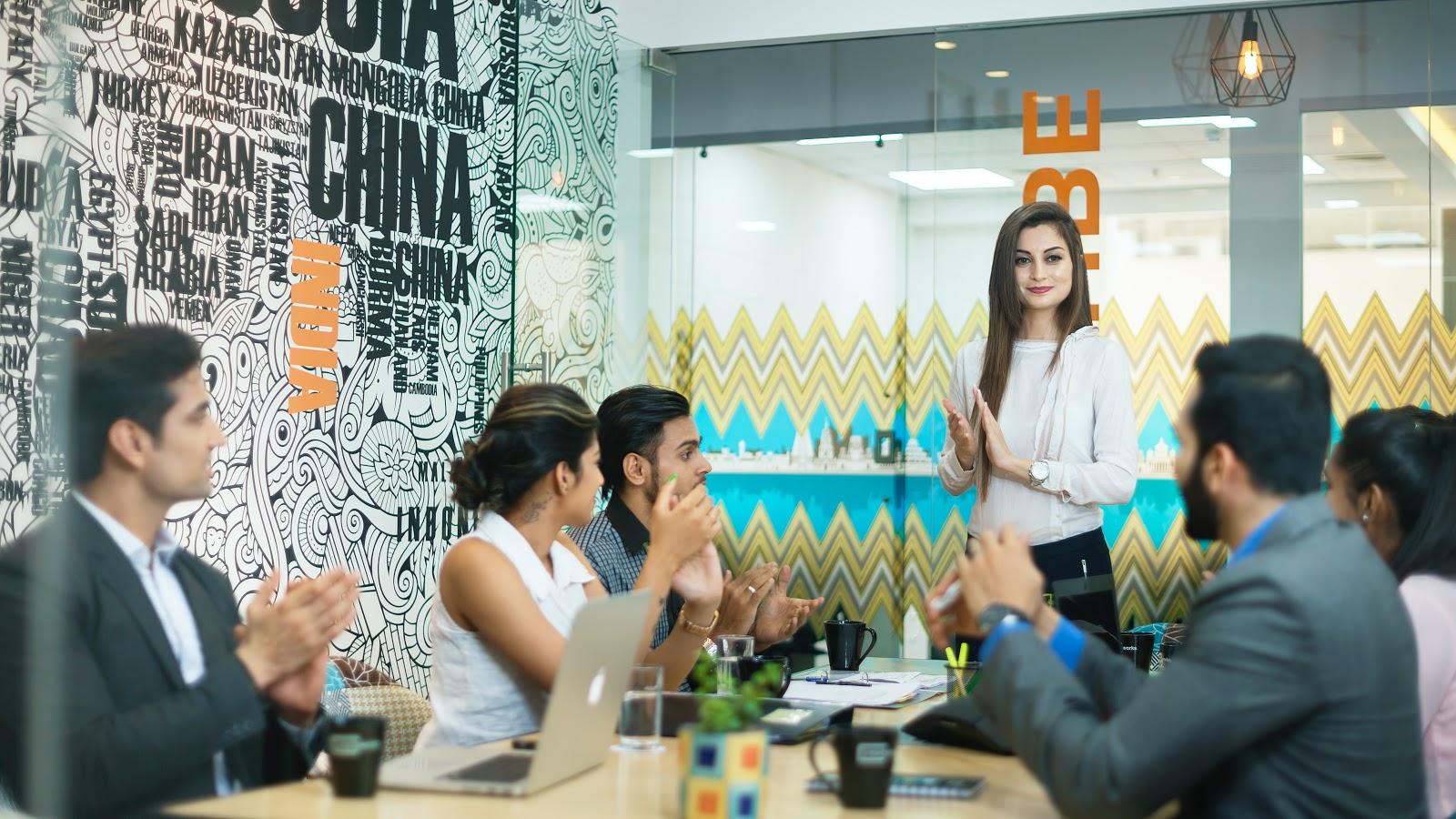 talent acquisition - Uma mulher de pé e outros funcionários sentados batendo palmas.