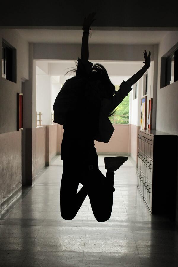 Silhueta de uma menina no corredor da escola pulando