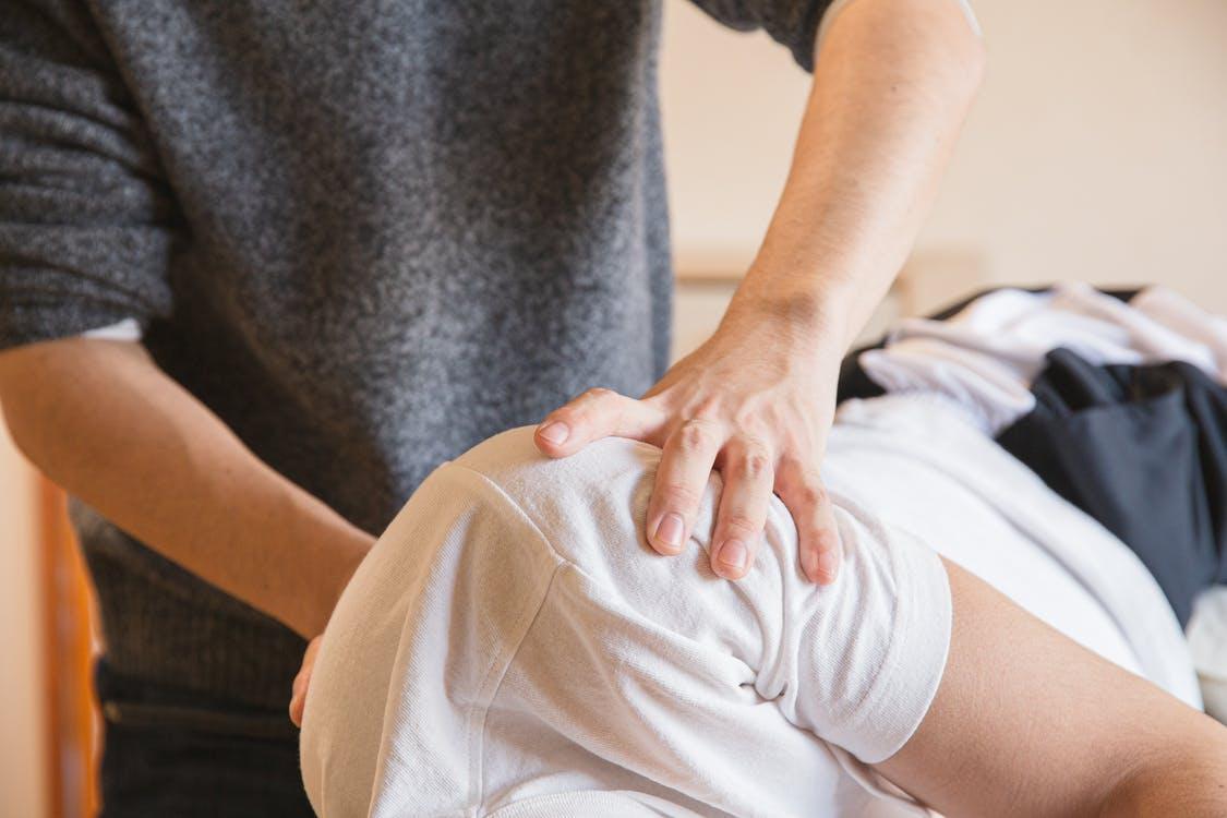 Crop masseur preparing client for spine treatment