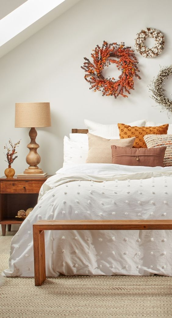 Bedroom with white walls white bedding and natural wood furniture. Warm orange and neutral shade throw pillows as well as orange and white berry wreaths on the wall.
