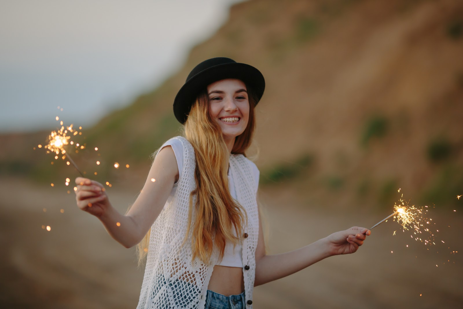 A young woman outside in the desert with sparklers