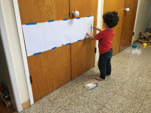 Toddler coloring on long piece of paper