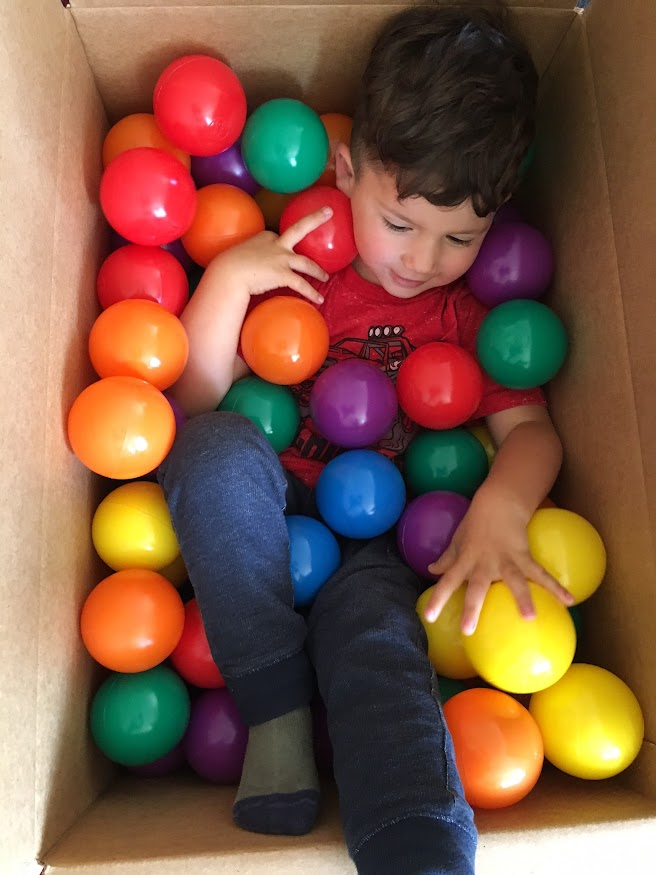 toddler in box with balls