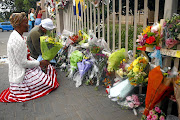 Members of the community  lay flowers at the gate of Driehoek school, where four children have  died after a walkway  collapse.