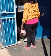 The teacher falls to the ground, inside her classroom.