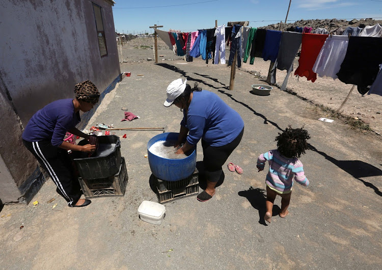 Melvina Adams and Michelle Fink of Hillside do their washing in a bucket in Beaufort West on November 08, 2017.