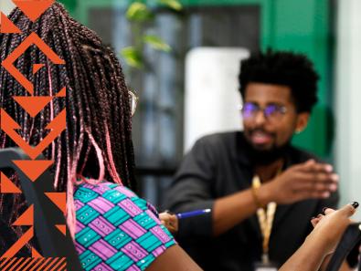 Foto de duas pessoas negras conversando em um escritório. Na lateral esquerda da foto há uma padronagem em laranja.