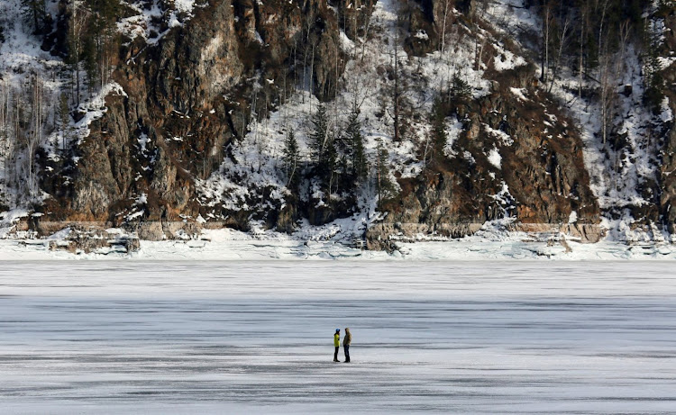 A couple talks on a frozen river in Russia.