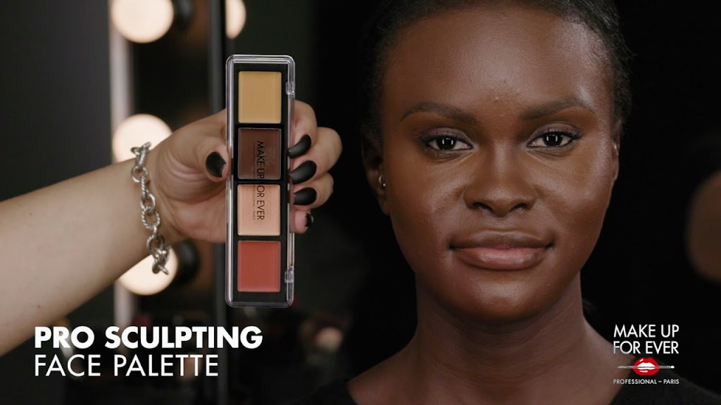 A frame from the Makeup Forever video showing a Black model's face next to a makeup palette.