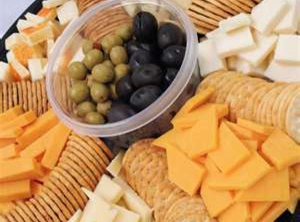 Sourround Crock with all the cheeses, add Crackers and sesame stks, & Vegies, in...