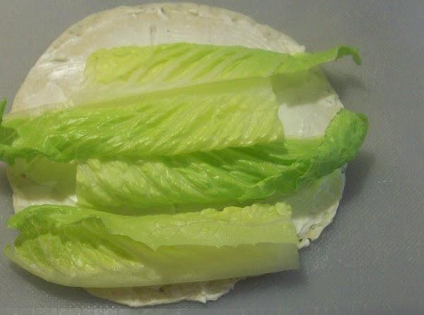 Lay 1 romaine leaf cut into quarters on top of the cream cheese.