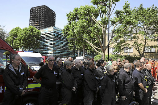 Members of the emergency services attend a minute's silence for the victims of the Grenfell Tower fire near the site of the blaze in north Kensington, London, on June 19 2017. Picture: Reuters/Marko Djurica
