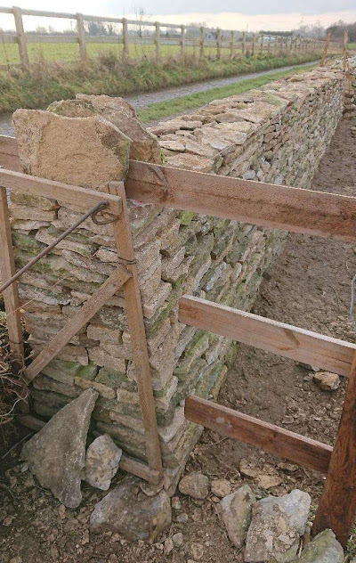 A dry stone waller uses an A-frame as a guide for the profile of a wall-end