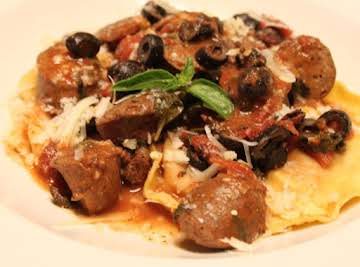 Black olive sauced chicken sausage with red pepper and tomato ravioli