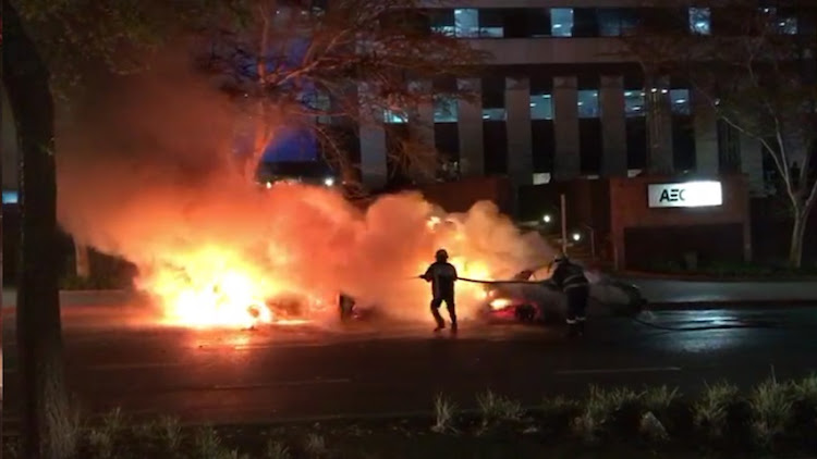 An Uber driver's vehicle burns during clashes with metered taxi divers in Sandton on Thursday night. Picture: SUPPLIED