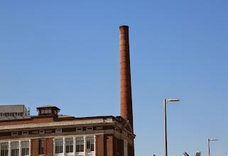 Photo: Một ống khói cổ của nhà máy xưa vẫn còn sừng sửng ngay trung tâm thành phố.