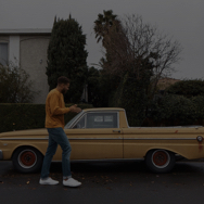 Man outside, wearing a yellow sweater, in front of a yellow car