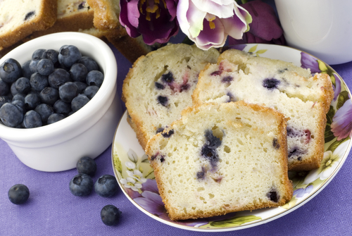 blueberries in a bowl next to a slice of blueberry pound cake