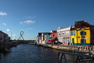 Photo: Hemos terminado el paseo en barco y caminamos por el barrio de los pescadores con sus coloridas casas. Detrás de mí, está la lonja y la Praça do Peixe. Al fondo el puente del lazo que vimos desde el agua, sobre el Canal de San Roque.