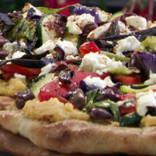 Grilled Pizza with Spicy Hummus, Vegetables, Goat Cheese and Black Olives.