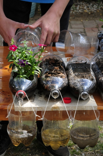 This is the fully assembled project with three two-liter bottles, each containing different soil situations. One of the bottles has vegetation in it. All three bottles have a run-off collection bin hanging from the neck of the bottle.