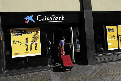 A man carrying a suitcase goes into a CaixaBank branch in Barcelona, Spain, October 5, 2017. REUTERS/SUSANA VERA