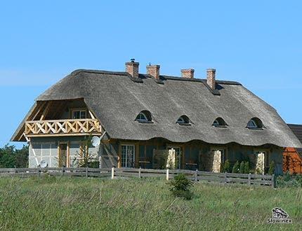 Podłużny dom z szarego muru pruskiego z pokryciem trzcinowym