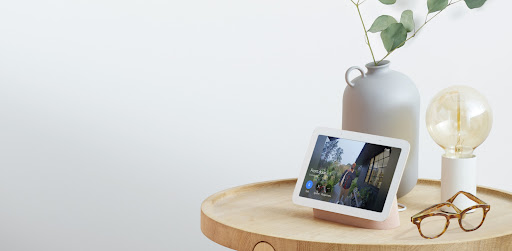 Nest Hub (2nd gen) is on a wooden table inside a home. On the display, a delivery person is at the front door holding a package.