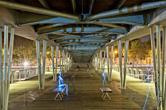 """Photo: Passerelle Simone de Beauvoir II  Last night, I went out for a photowalk in Paris, near a place called """"Bibliothèque Francois Mitterand"""", a huge library. A superb bridge crosses the Seine river.. I had to shoot it !  I especially like the two guys, sitting in the background. They were looking at me probably thinking """"What the hell is he doing !?"""" ^^ You can see my jeans and shoes. Next time I ll be a """"man in black"""", no more visible clothes on the photographs !  More to come. Light is Life !"""